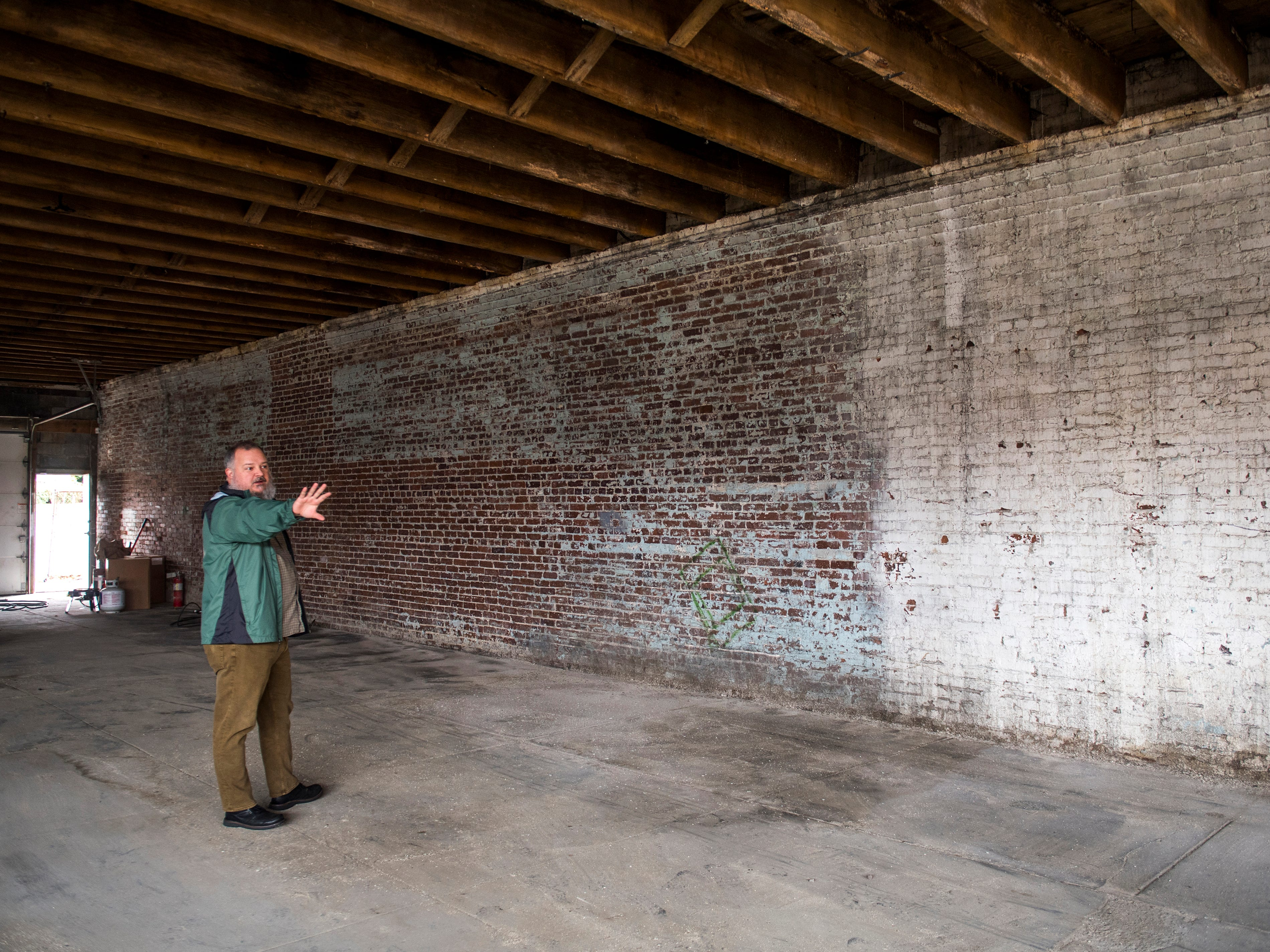 Next Level Brewing Company business partner Andrew Armstrong points out where the brewery portion will be inside their location at 700 N. Broadway in Knoxville on Jan. 3, 2019.
