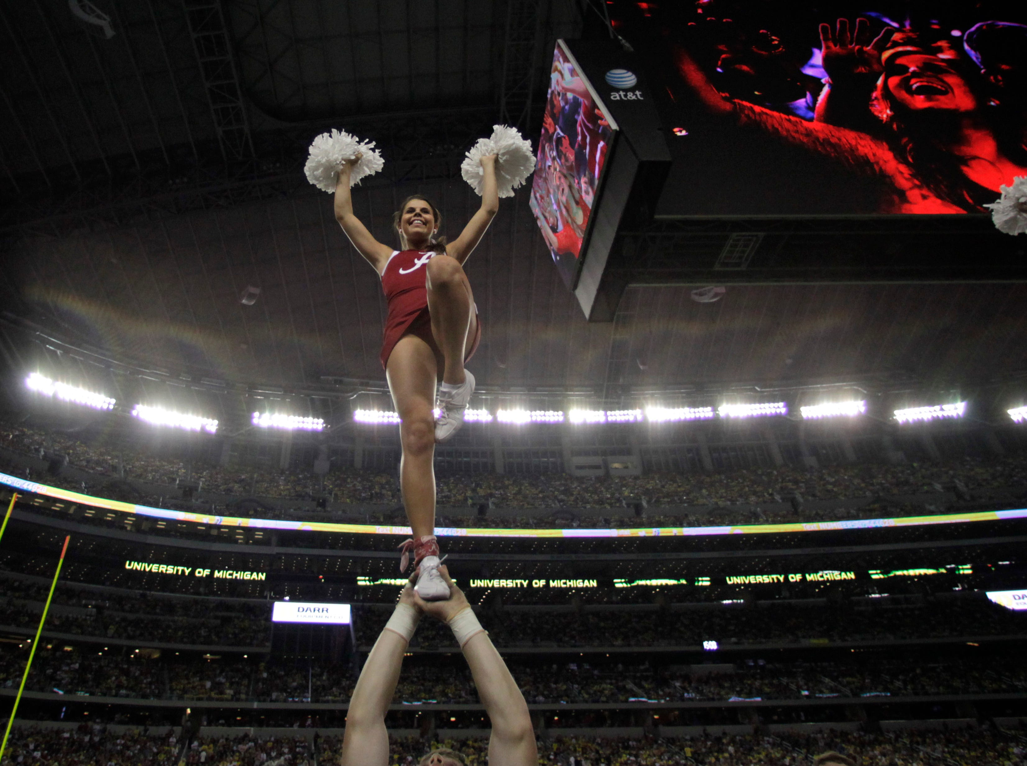 An Alabama cheerleader his held high during the second half of the NCAA college football game against  Michigan at Cowboys Stadium in Arlington, Texas, Saturday, Sept. 1, 2012. McCarron threw two touchdown passes in the Alabama  41-14 win.  (AP Photo/LM Otero)