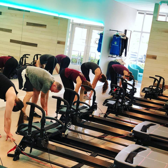 A class at Core Change Fitness has men and women stretching before working out on the Megaformer machine.