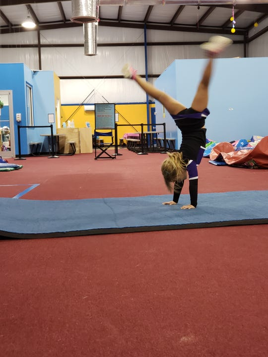 Alleah Clark does a handstand through a routine.