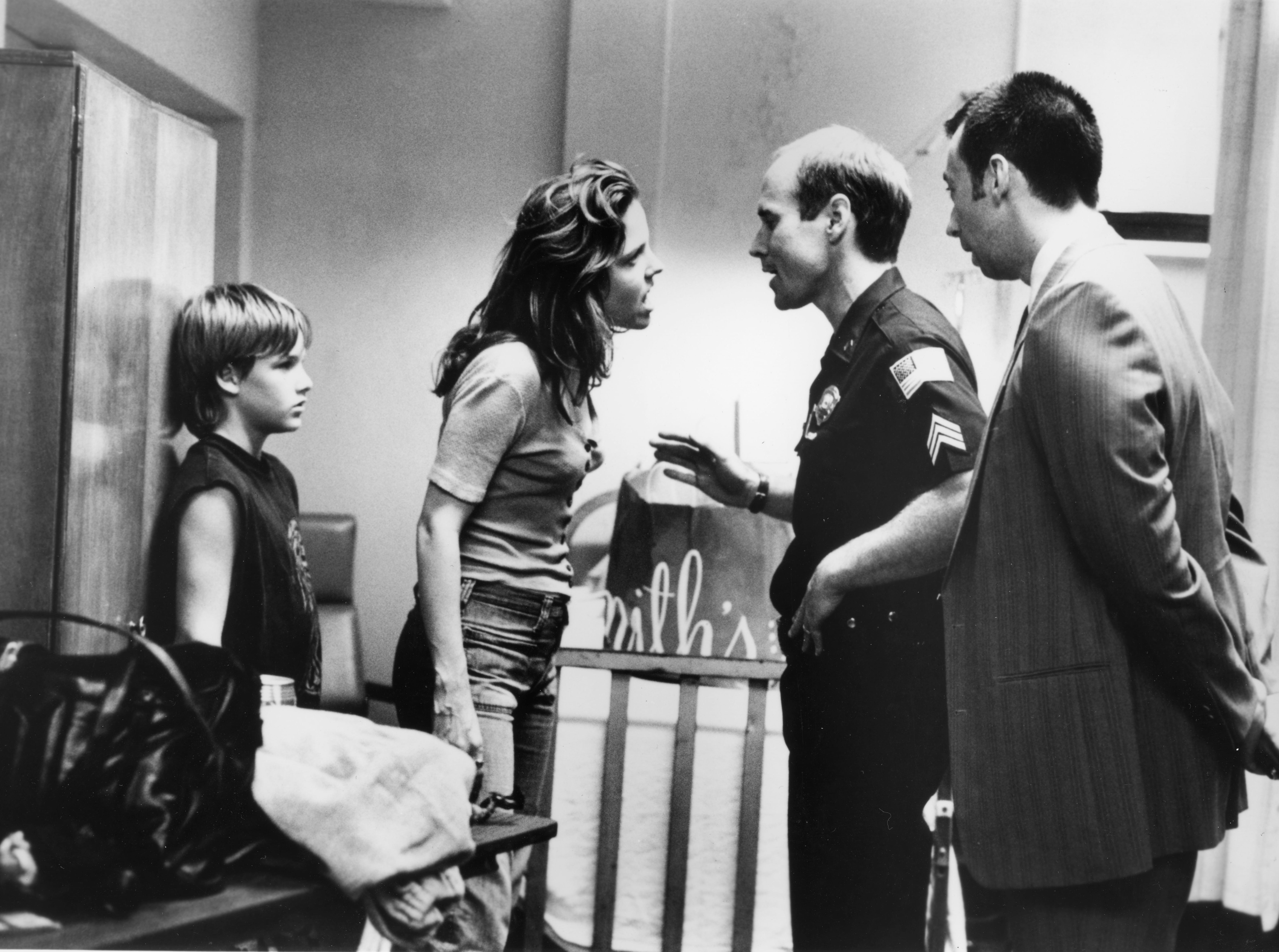 "Young Mark Sway (Brad Renfro) and his mother, Dianne Sway (Mary-Louise Parker), face the intimidating questions of Sgt. Hardy (Will Patton) and Detective Nasser (Mark Cabus) in Warner Bros.' suspense-thriller, ""The Client"", based on the best-selling novel by John Grisham and starring Susan Sarandon and Tommy Lee Jones."