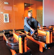 "Orangetheory Fitness owner Chris Davis demonstrates a water rowing machine. ""The water creates the resistance,"" he said."
