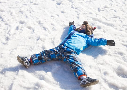 Four-year-old Andrew Rizik, visiting Mt. Brighton with his family from Maumee, Ohio, takes advantage of the white stuff they don't currently have back home to make snow angels Thursday, Jan. 3, 2019.