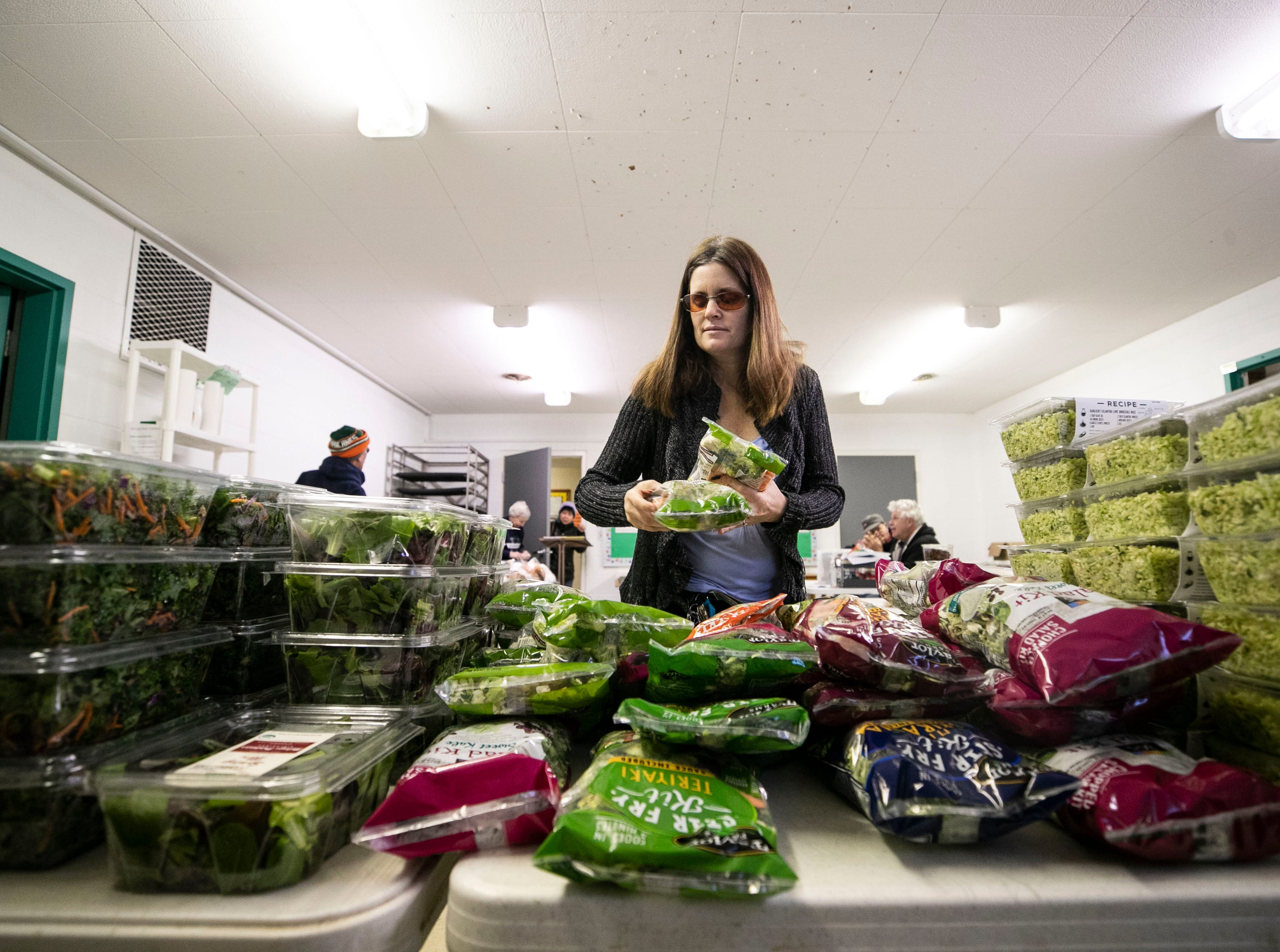 Suzanne De Gregorio of the St. Matthews Area Ministries Food Pantry helps organize donated greens from Whole Foods for those in need before opening at the Beechwood Baptist Church. Three times a week the food pantry opens for a few hours that allow people in need a chance to get food.