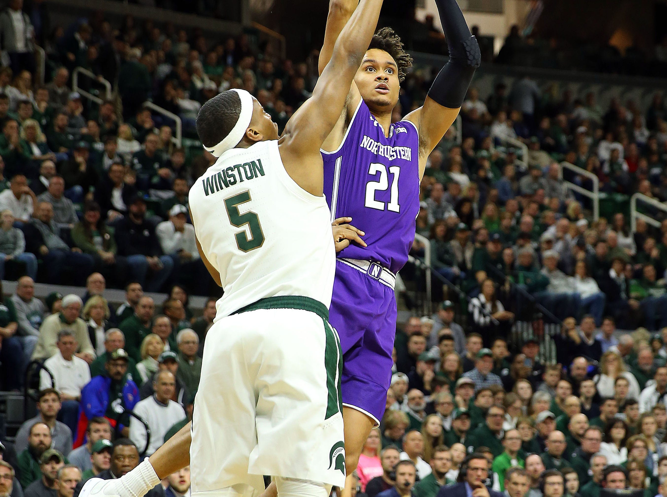 Jan 2, 2019; East Lansing, MI, USA; Northwestern Wildcats forward A.J. Turner (21) is defended by Michigan State Spartans guard Cassius Winston (5) during the first half of a game at the Breslin Center. Mandatory Credit: Mike Carter-USA TODAY Sports