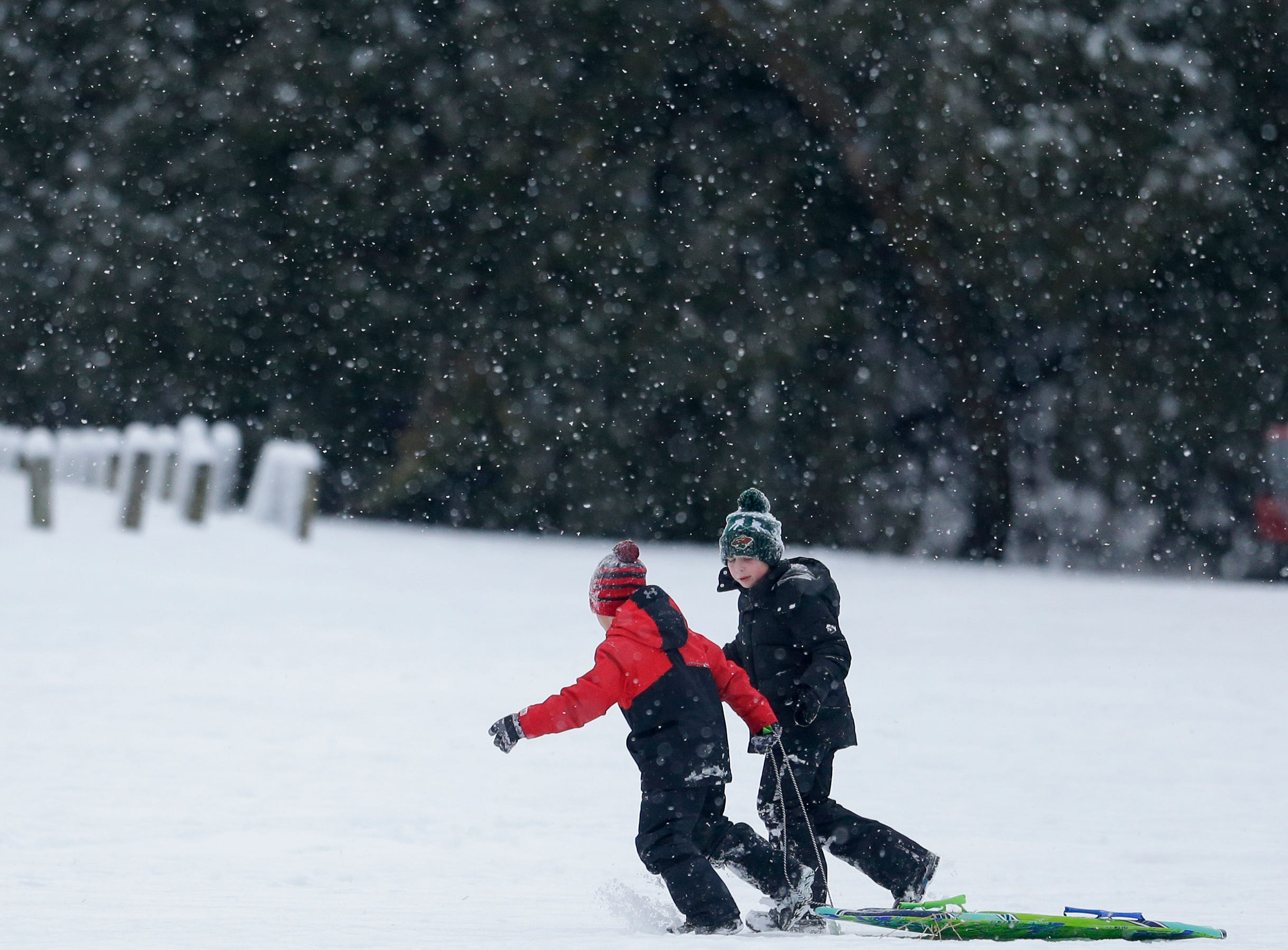 Miles Rice, 7, and Padraic Dunn, 7, run their sled back up the hill at Silver Creek Park during a snowfall Wednesday, January 2, 2019, in Manitowoc, Wis. Joshua Clark/USA TODAY NETWORK-Wisconsin