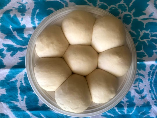 After a first rise, the dough is formed into eight balls and left to rise again.