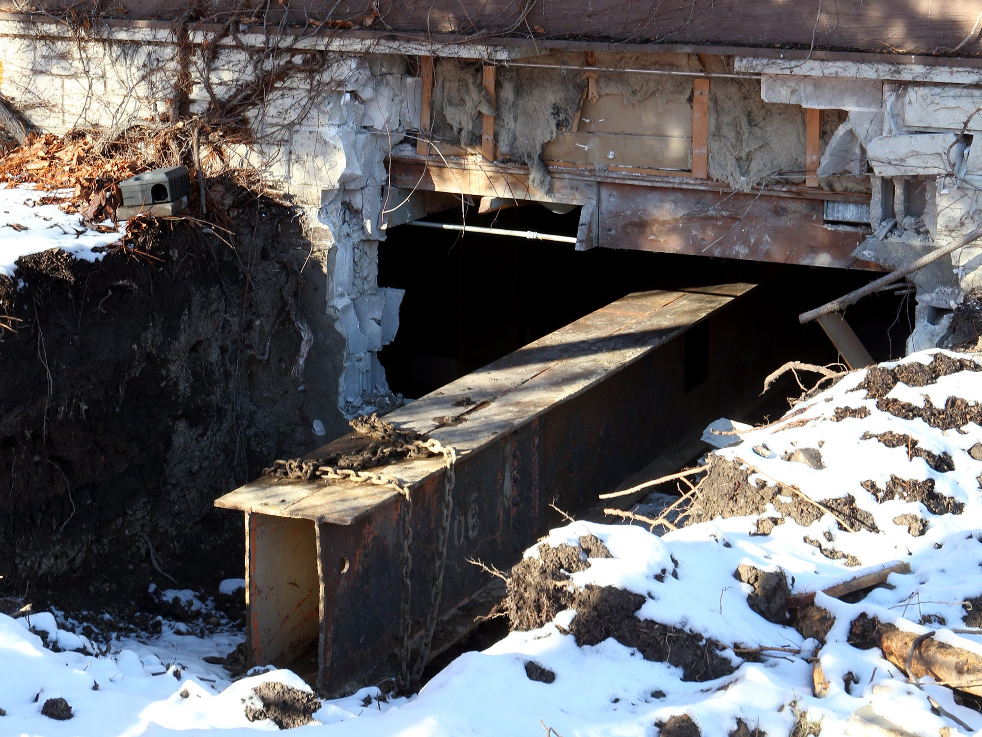 A steel beam pierces the foundation of the Log Cabin that is to be moved from 2515 N. Wauwatosa Ave. to a site on the northwest corner of North Avenue and 64th Street. A planned Jan. 9 move has been postponed.