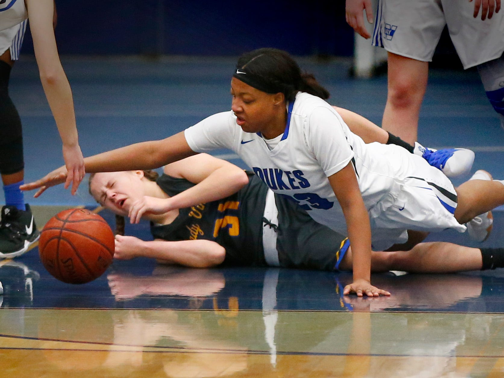 Whitefish Bay's Emeria McPherson stretches over New Berlin West's Makenna Huguet for a loose ball at Whitefish Bay on Jan. 2.
