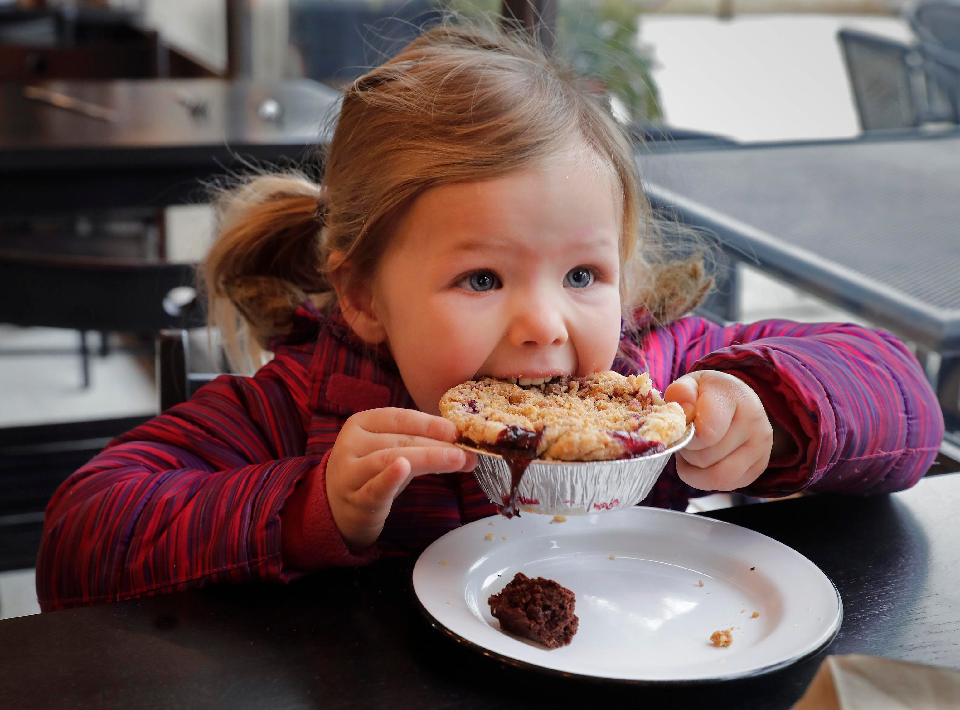 Maisie Naus, 3, bites into a cherry small pie at SmallPie, 2504 E. Oklahoma Ave. in Bay View, a tiny counter-service cafe featuring sweet and hand small pies.