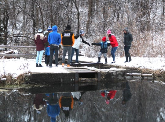 A group of hikers cross a plank over the outlet of Paradise Springs pond in the Kettle Moraine State Forest - Southern Unit near Eagle.