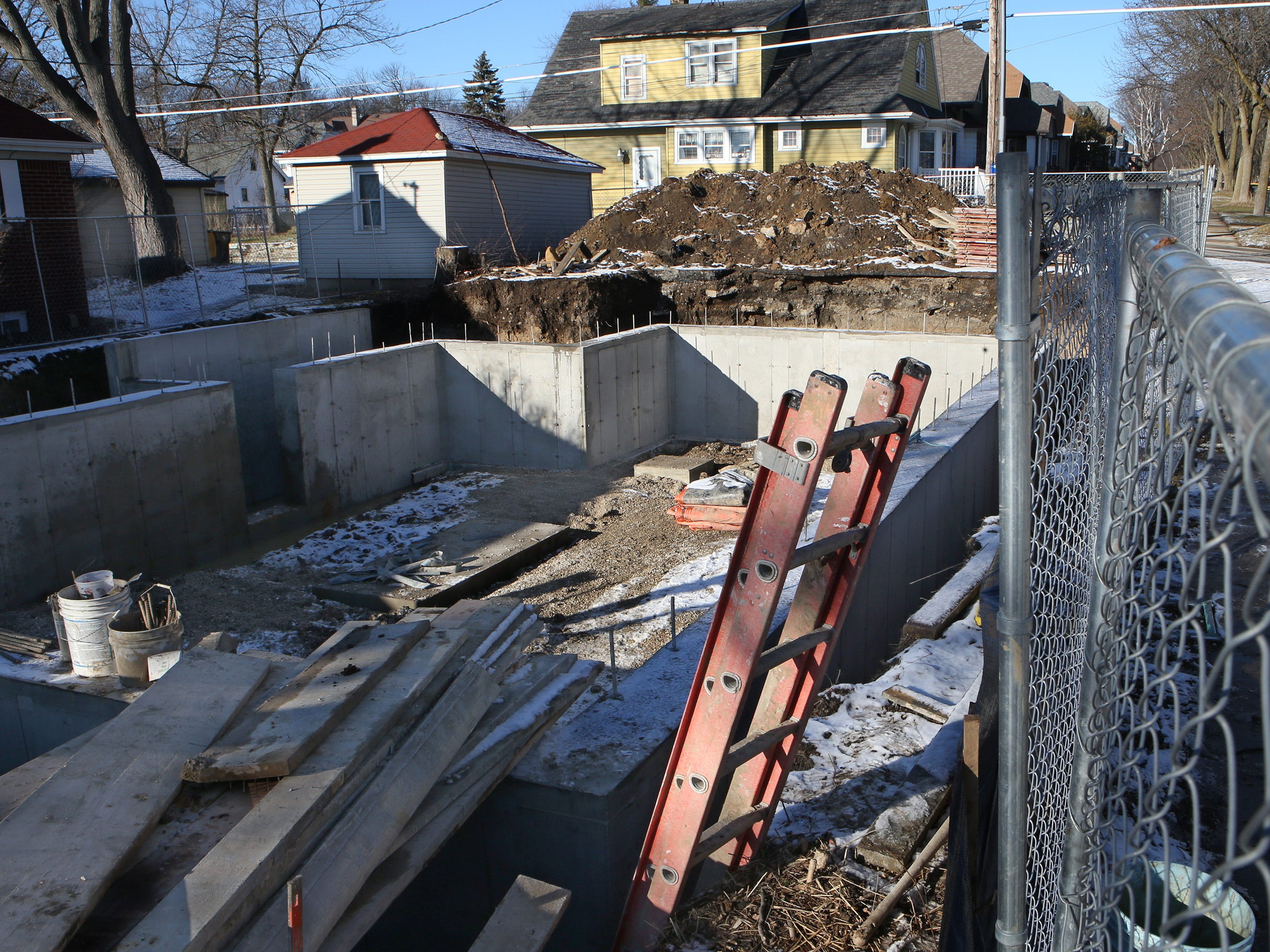 A foundation is in place to receive the Log Cabin that is to be moved from 2515 N. Wauwatosa Ave. to this site on the northwest corner of North Avenue and 64th Street. A planned Jan. 9 move has been postponed.