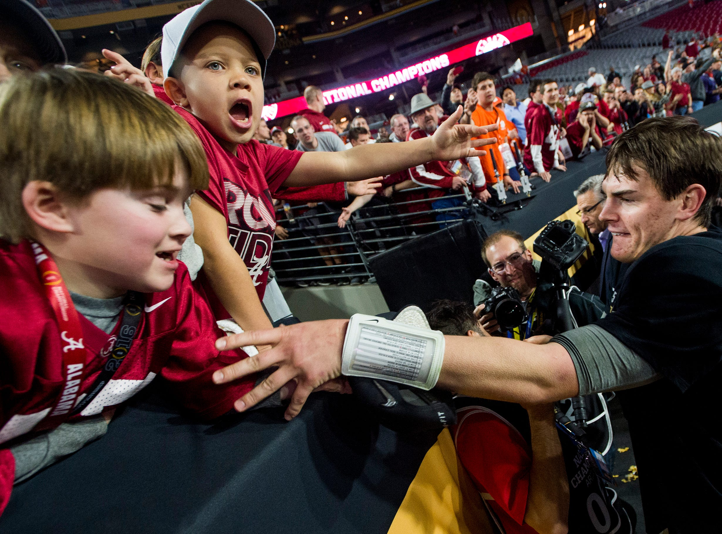 Alabama quarterback Jake Coker (14) gives his championship cap to kids in the stands following the College Football Playoff Championship Game on Monday January 11, 2016 at University of Phoenix Stadium in Glendale, Az.