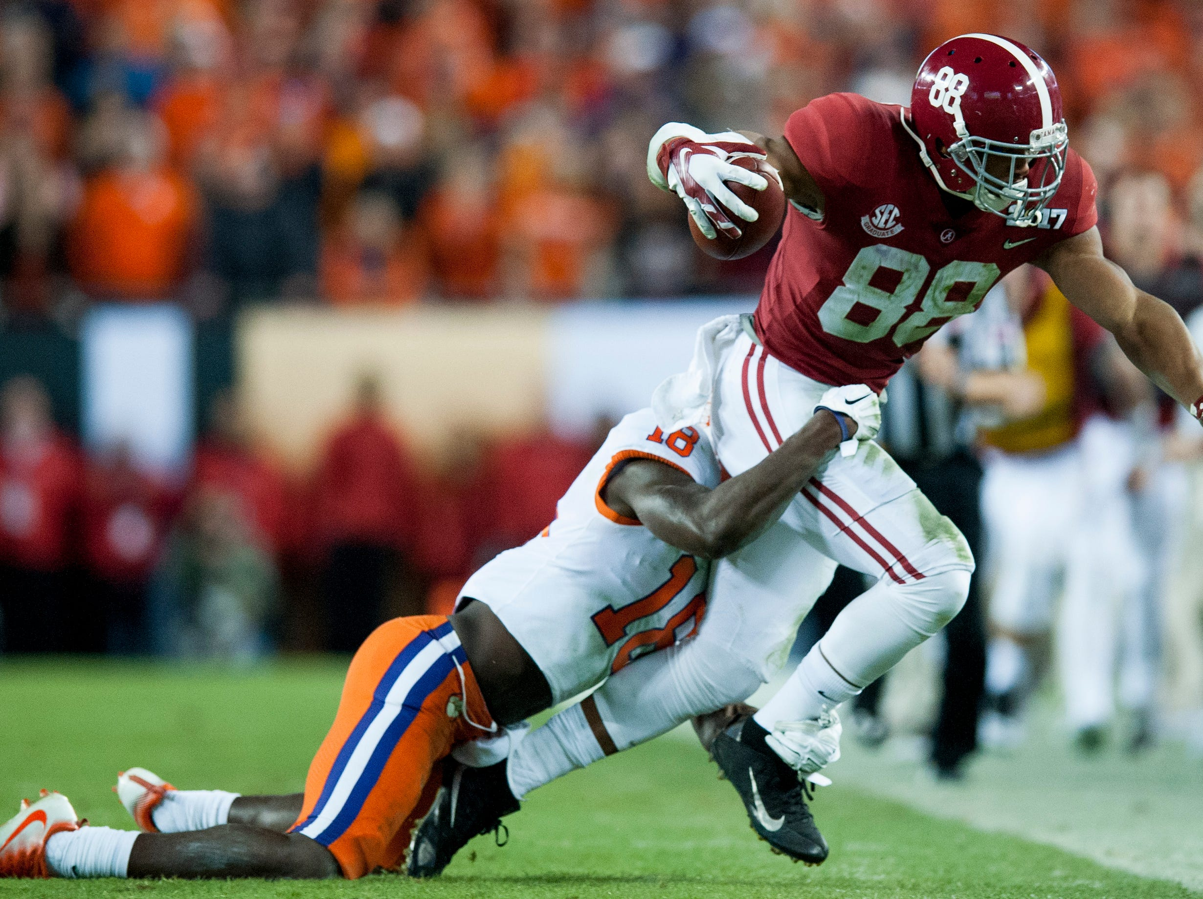 Alabama tight end O.J. Howard (88) is stopped by Clemson safety Jadar Johnson (18) after catching a pass from a receiver in second half action of the College Football Playoff National Championship Game at Raymond James Stadium in Tampa, Fla. on Monday January 9, 2017.