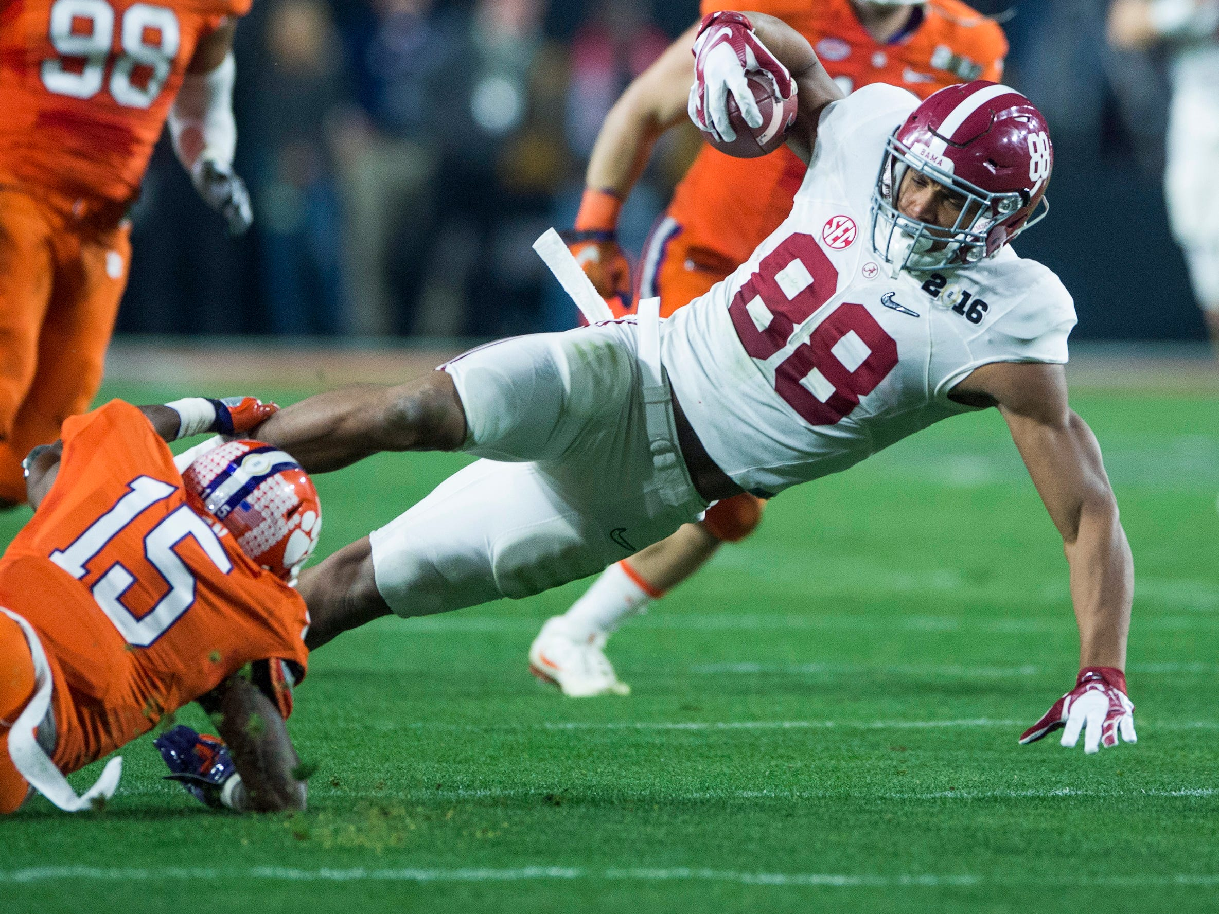 Alabama tight end O.J. Howard (88) is tripped up by Clemson safety T.J. Green (15) in the College Football Playoff Championship Game on Monday January 11, 2016 at University of Phoenix Stadium in Glendale, Az.