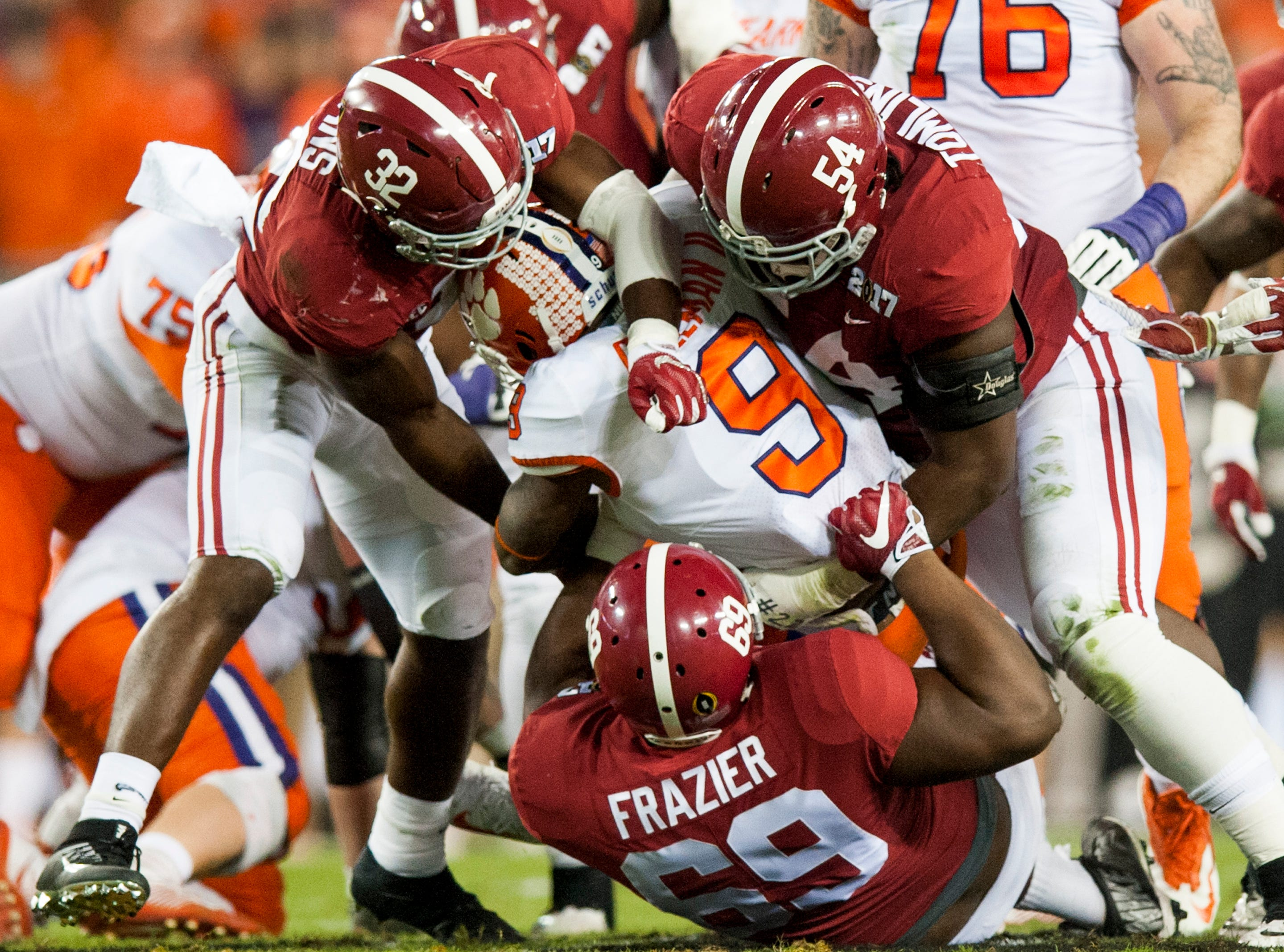 Clemson running back Wayne Gallman (9) is tackled by Alabama linebacker Rashaan Evans (32), defensive lineman Dalvin Tomlinson (54) and defensive lineman Joshua Frazier (69) in first half action of the College Football Playoff National Championship Game at Raymond James Stadium in Tampa, Fla. on Monday January 9, 2017.