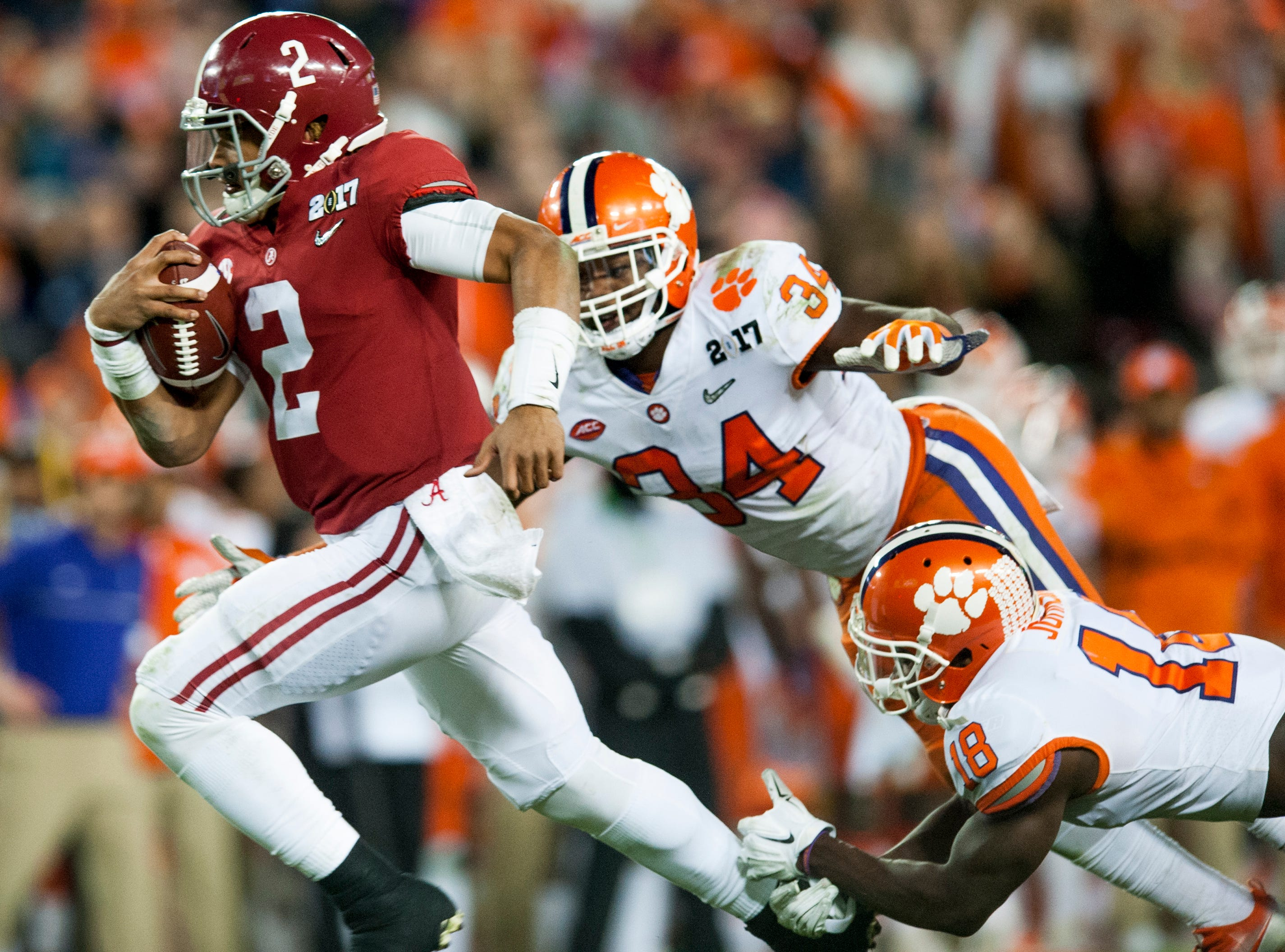 Alabama quarterback Jalen Hurts (2) breaks away from Clemson linebacker Kendall Joseph (34) and Clemson safety Jadar Johnson (18) for a late touchdown in second half action of the College Football Playoff National Championship Game at Raymond James Stadium in Tampa, Fla. on Monday January 9, 2017.