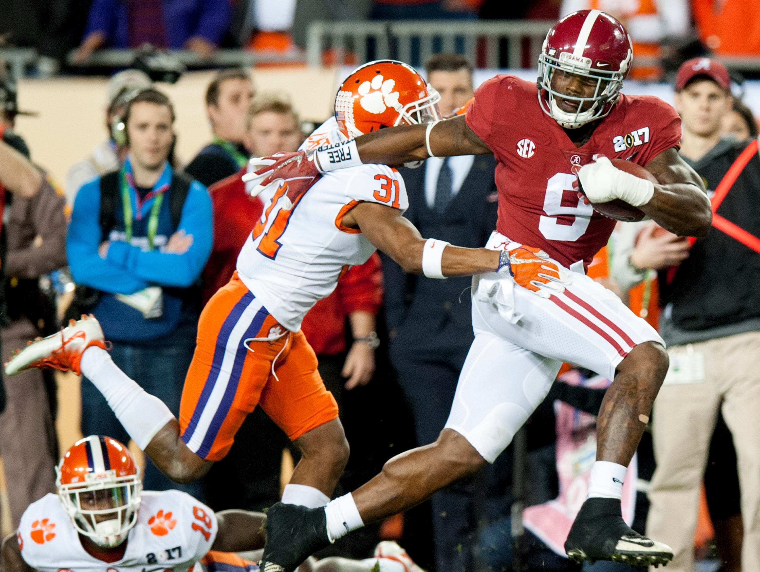 Alabama running back Bo Scarbrough (9) makes his way into the end zone for a first quarter touchdown against Clemson defensive back Ryan Carter (31) in the College Football Playoff National Championship Game at Raymond James Stadium in Tampa, Fla. on Monday January 9, 2017.