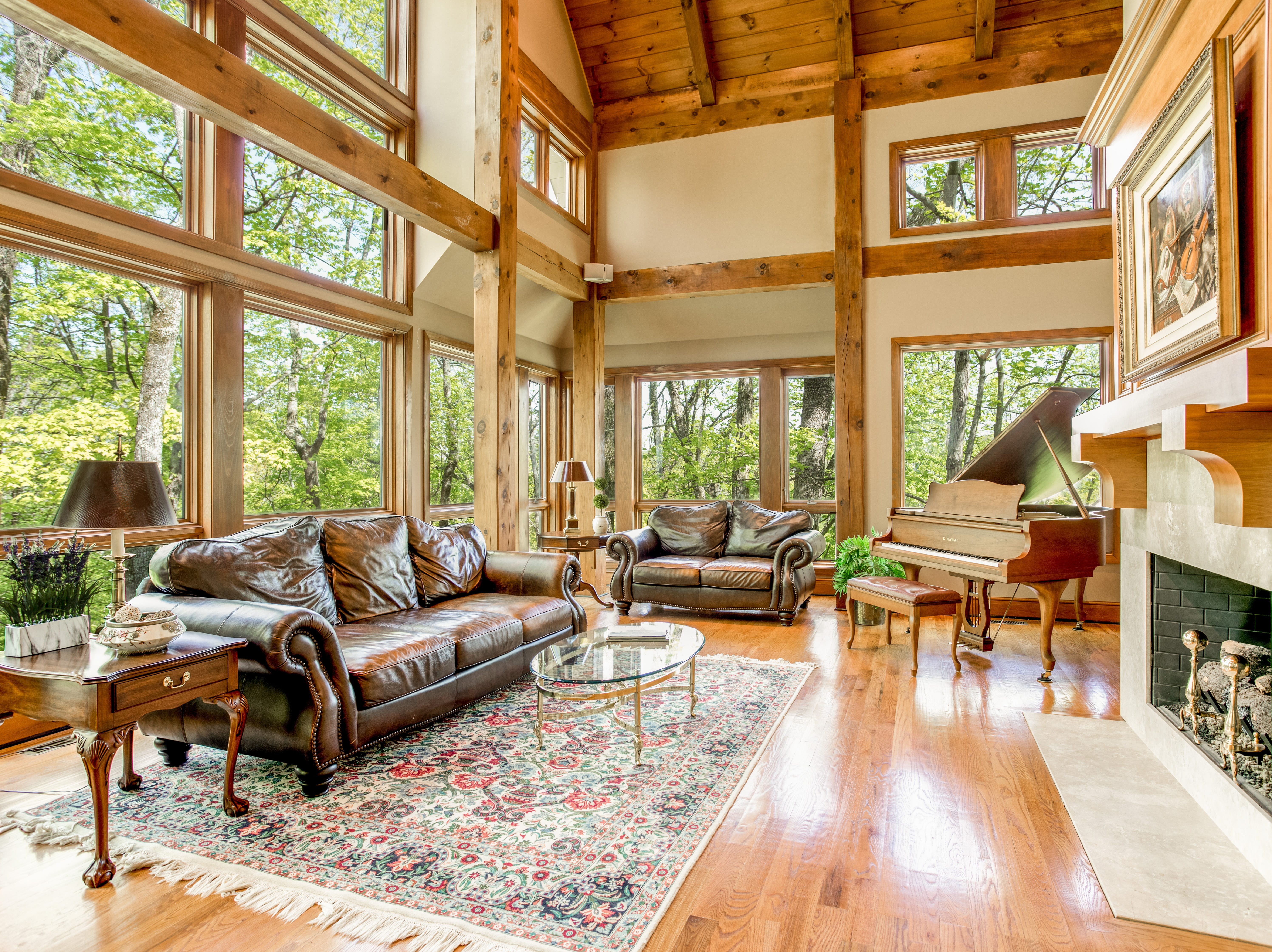 The home's main living space is full of windows and is post and beam construction, which exposes the beams for a rustic, mountain look.