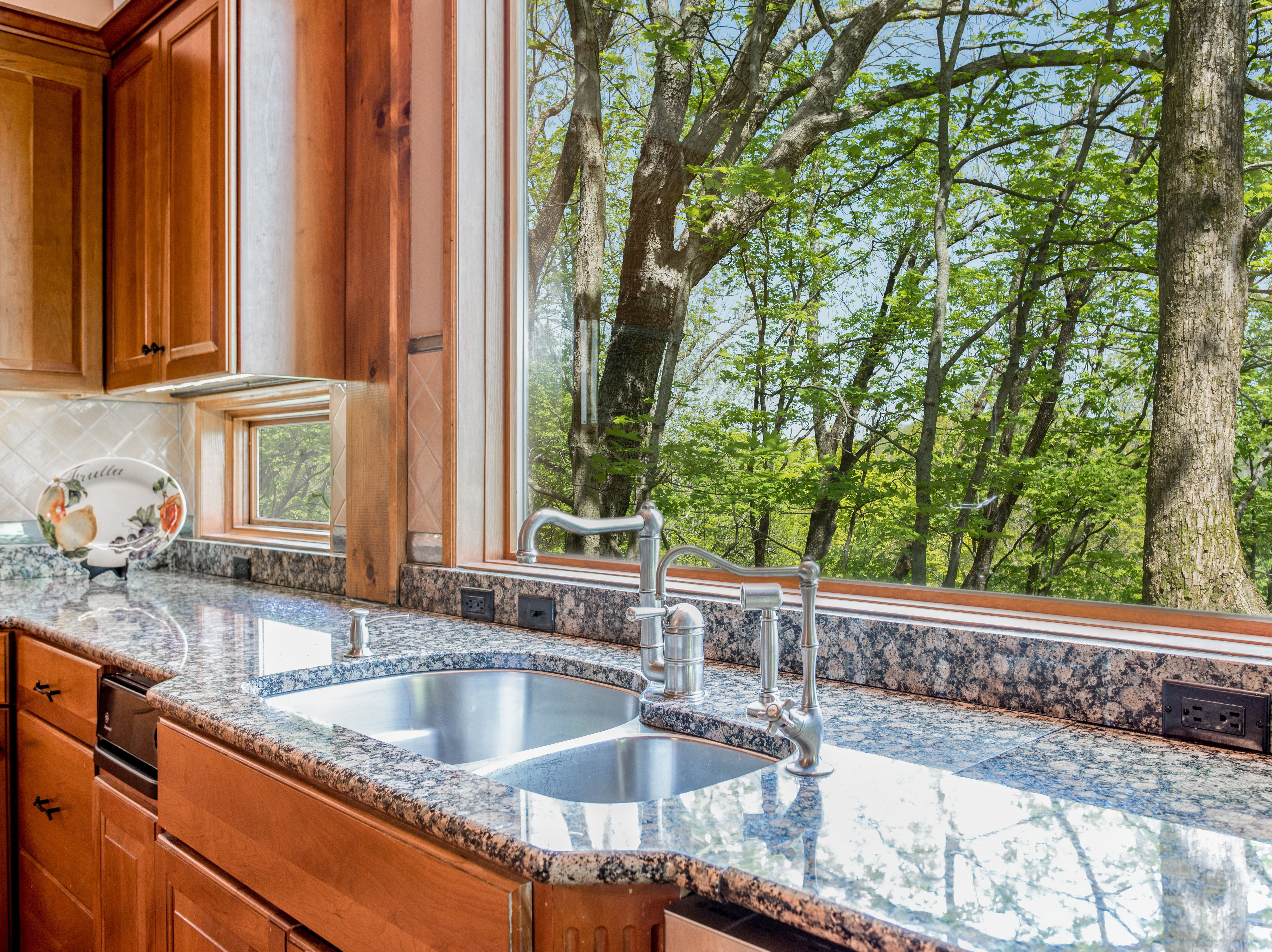 The picture window over the kitchen sink provides beautiful views of the 11 acres of land this home sits on.