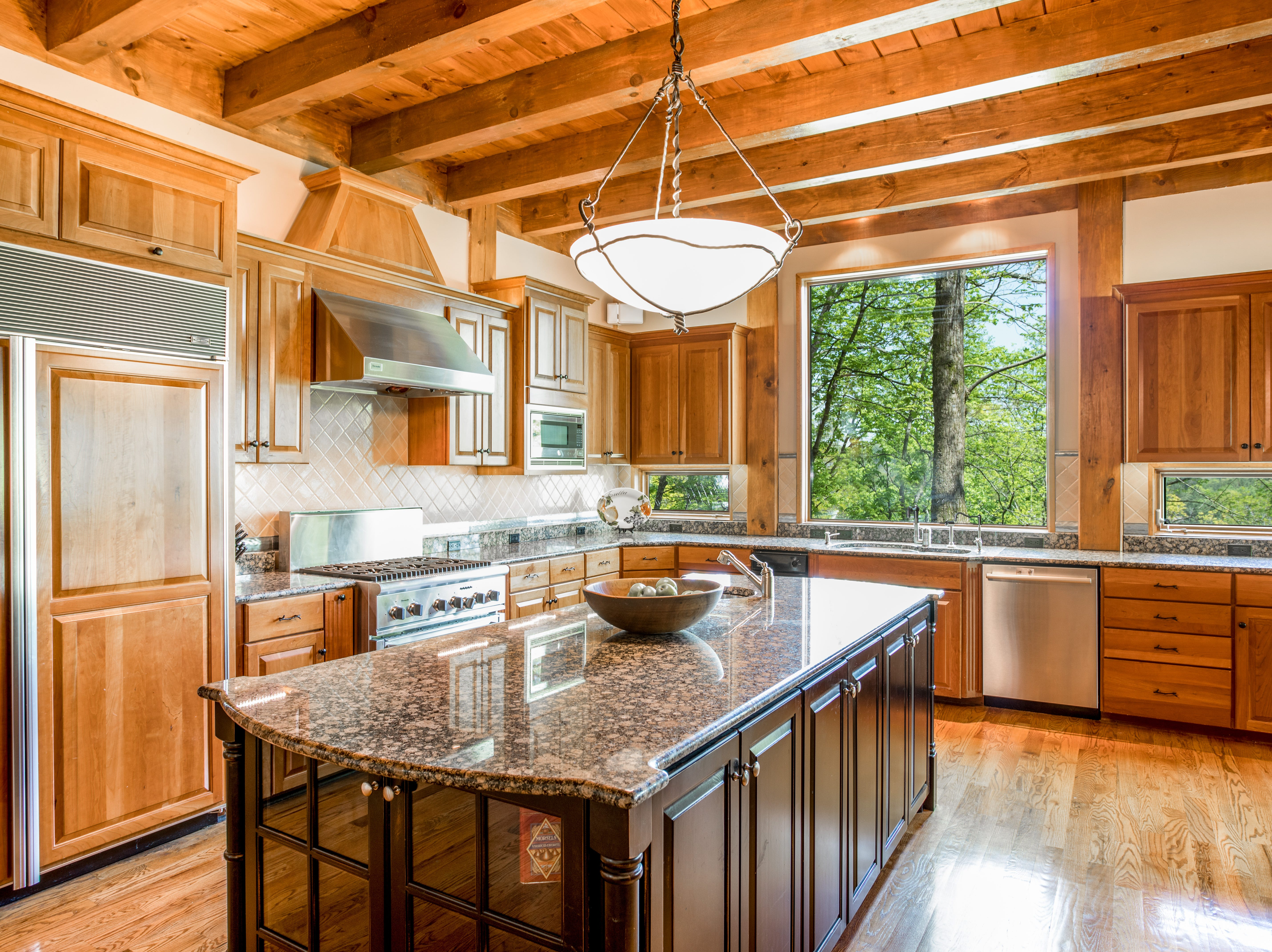 The kitchen features an oversized island and beautiful views of the surrounding land.