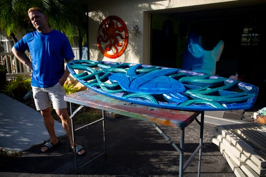 Jake Jones describes his process for creating his surfboard artwork on Wednesday, Jan. 2, 2019, at his home in Golden Gate Estates.