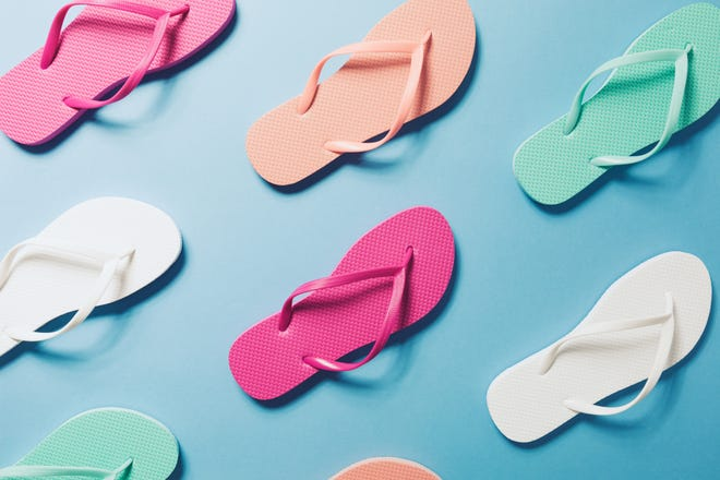 Overhead view of flip flops on a blue background.