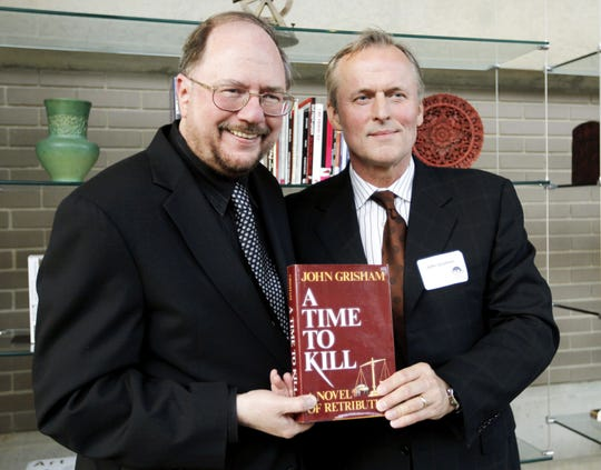 "Playwright Rupert Holmes, left, and author John Grisham pose with Grisham's book ""A Time to Kill"" at the world premiere of the stage adaptation at Arena Stage theater in Washington, D.C., on Sunday, May 22, 2011."