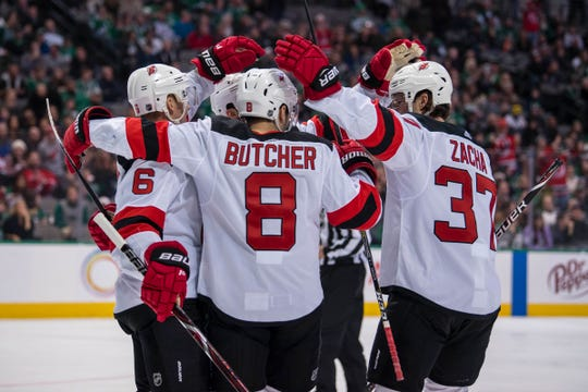 New Jersey Devils right wing Kyle Palmieri (21) and defenseman Andy Greene (6) and defenseman Will Butcher (8) and center Pavel Zacha (37) celebrates scoring a goal against the Dallas Stars during the first period at the American Airlines Center.