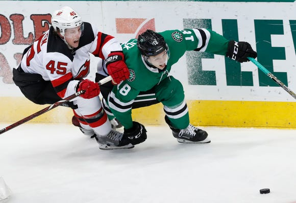 Dallas Stars center Tyler Pitlick (18) and New Jersey Devils defenseman Sami Vatanen (45) skate for the puck during the second period of an NHL hockey game in Dallas, Wednesday, Jan. 2, 2019.