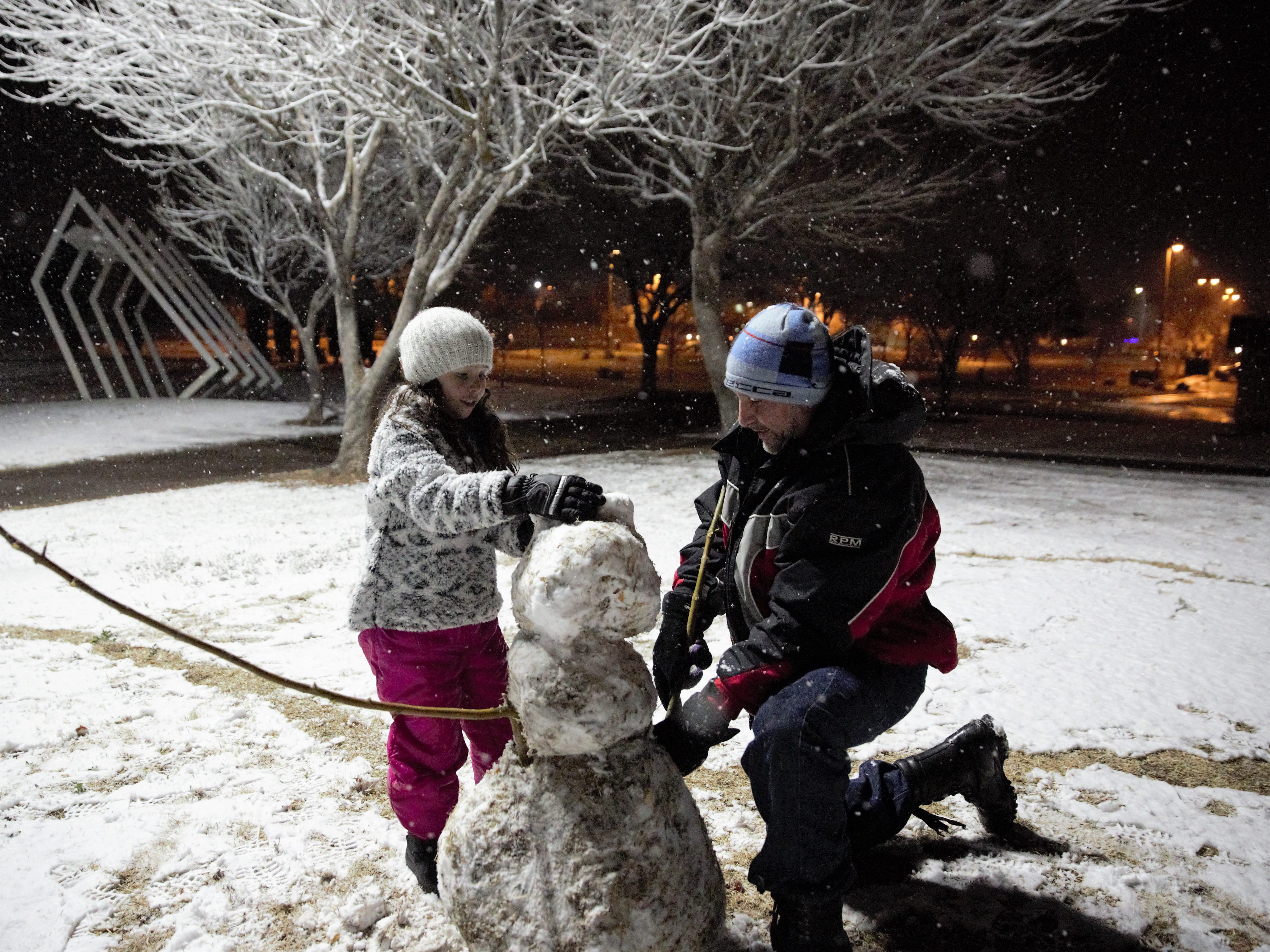 Maria Chavez, 9, left, and her father, James Chavez, work to build a snowman at Young Park in Las Cruces on the night of Wednesday, Jan. 2, 2019.