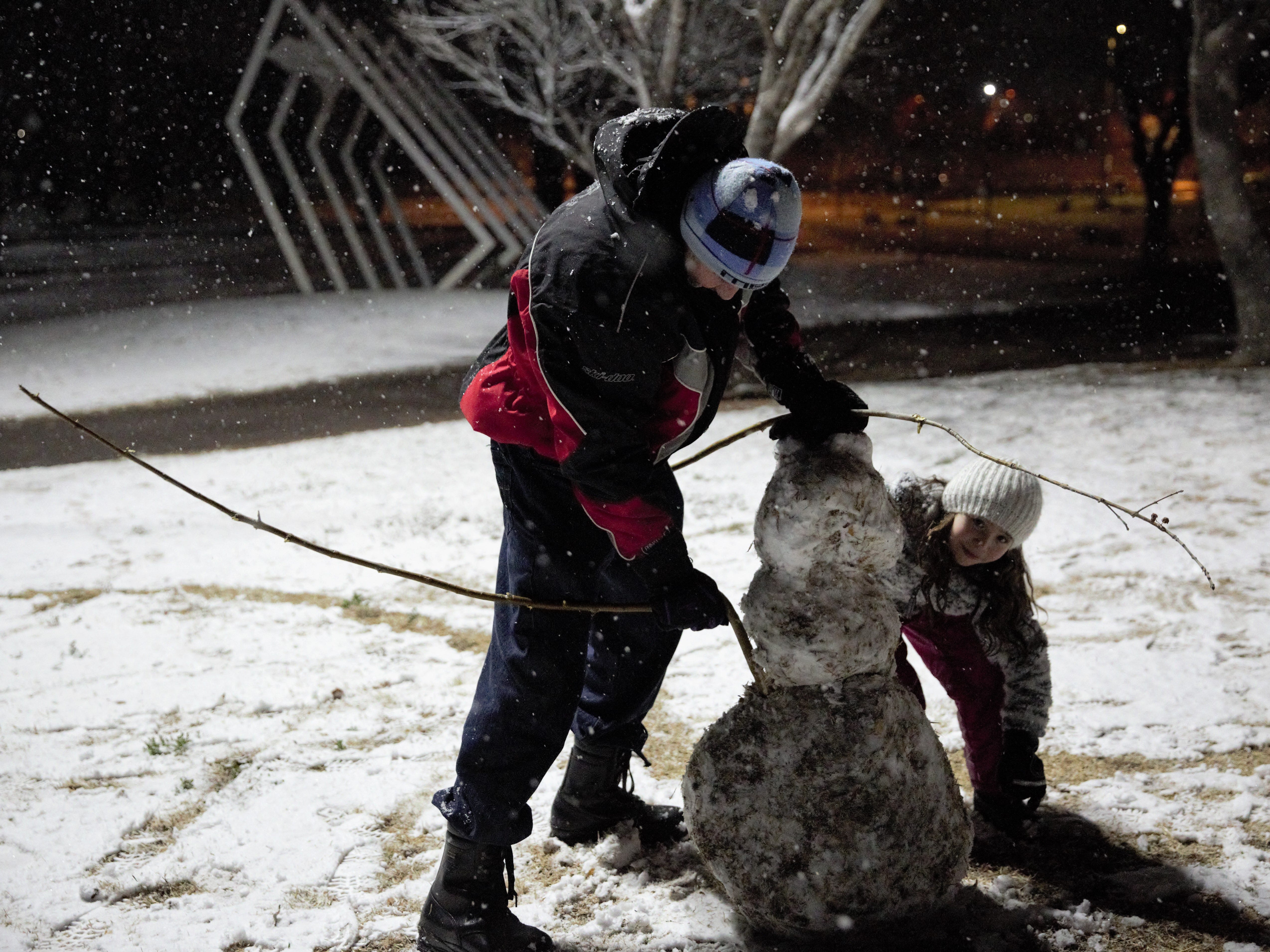 """James Chavez of Las Cruces installs a branch for a snowman's arm, as his daughter, Maria Chavez, 9, assists. The two took advantage of evening snowfall on Wednesday, Jan. 2, 2019, to play in the snow at Young Park. """"You only live once; it's important to get out here and have some fun,"""" James Chavez says."""