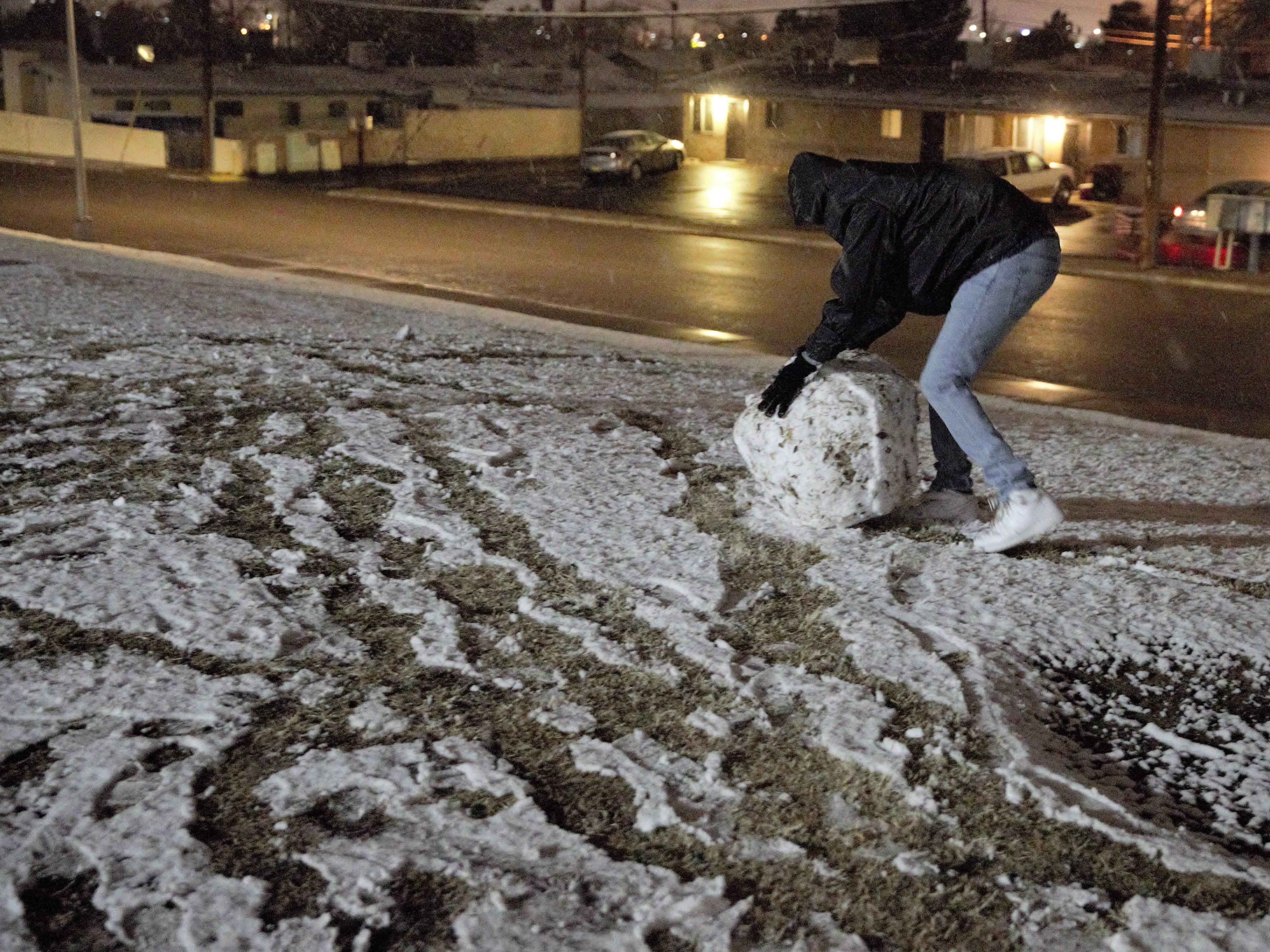 Las Crucen Issac Rojas, 14, forms a giant snowball that will become part of a snowman at Young Park on Wednesday, Jan. 2, 2019.