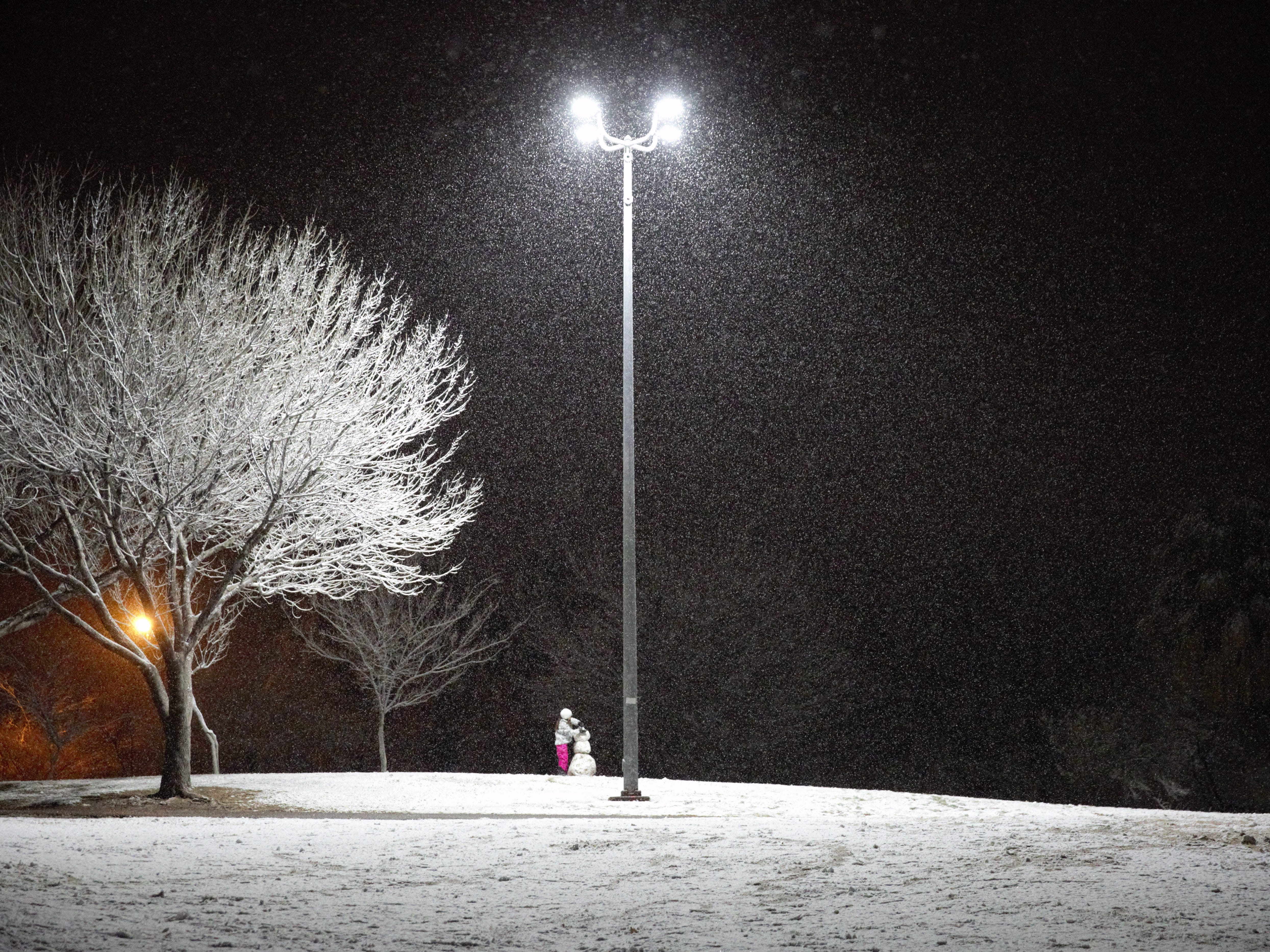 Maria Chavez, 9, of Las Cruces builds a snowman the night of Jan. 2, 2019 at Young Park.