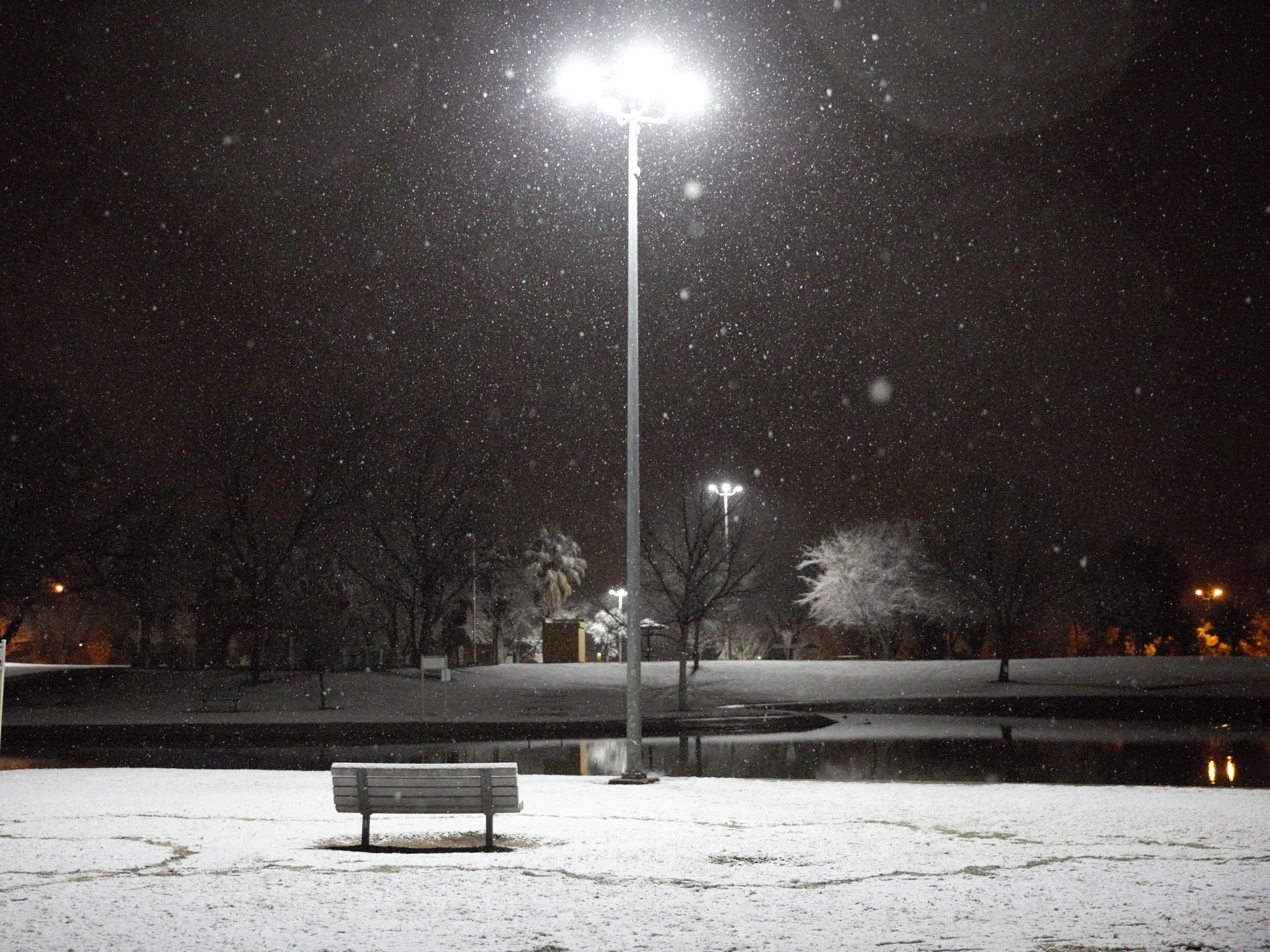 A trackway — the path taken by a teen building a snowman — winds through Young Park the night of Wednesday, Jan. 2, 2019, as snow continues to fall. The short-lived storm left a dusting of snow across Las Cruces.