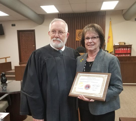 Lincoln County Treasurer Beverly Calaway holds her certificate of election. At left is 12th Judicial District Judge Dan Bryant, who administered the oaths of office.