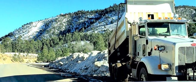 The snow gathered from Sudderth Drive is dropped on the wide shoulder along Grindstone near the intersection with Carrizo Canyon in Ruidoso.