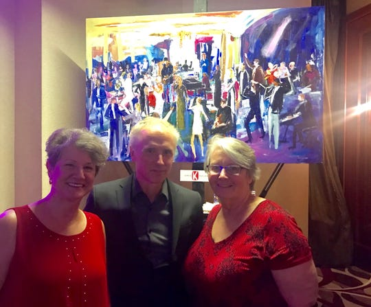 Christine Brown (left) and Ellen Weinstein (right) pose with artist Greg Kalamar in front of the just-completed painting they were delighted to win in the live auction