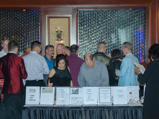 Bidders peruse the silent auction's many appealing items
