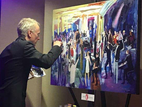 Live action artist Greg Kalamar paints the Desert Jam scene before him