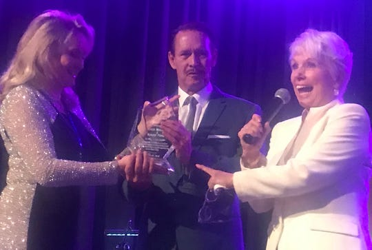 """I get a plaque, too? Hot dog!"" the ebullient Joyce Bullifant (right) says, as she receives her Jammy Award from Darci Daniels (left), with stepson Chris Perry assisting"