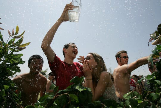 Reid Ulrich (left), 16, and Kelsey Westphal, 16, both of Ojai cool themselves off in a water feature during the afternoon to watch bands perform at the Coachella Valley Music and Arts Festival at the Empire Polo Fields on April 29, 2006 in Indio, Calif.