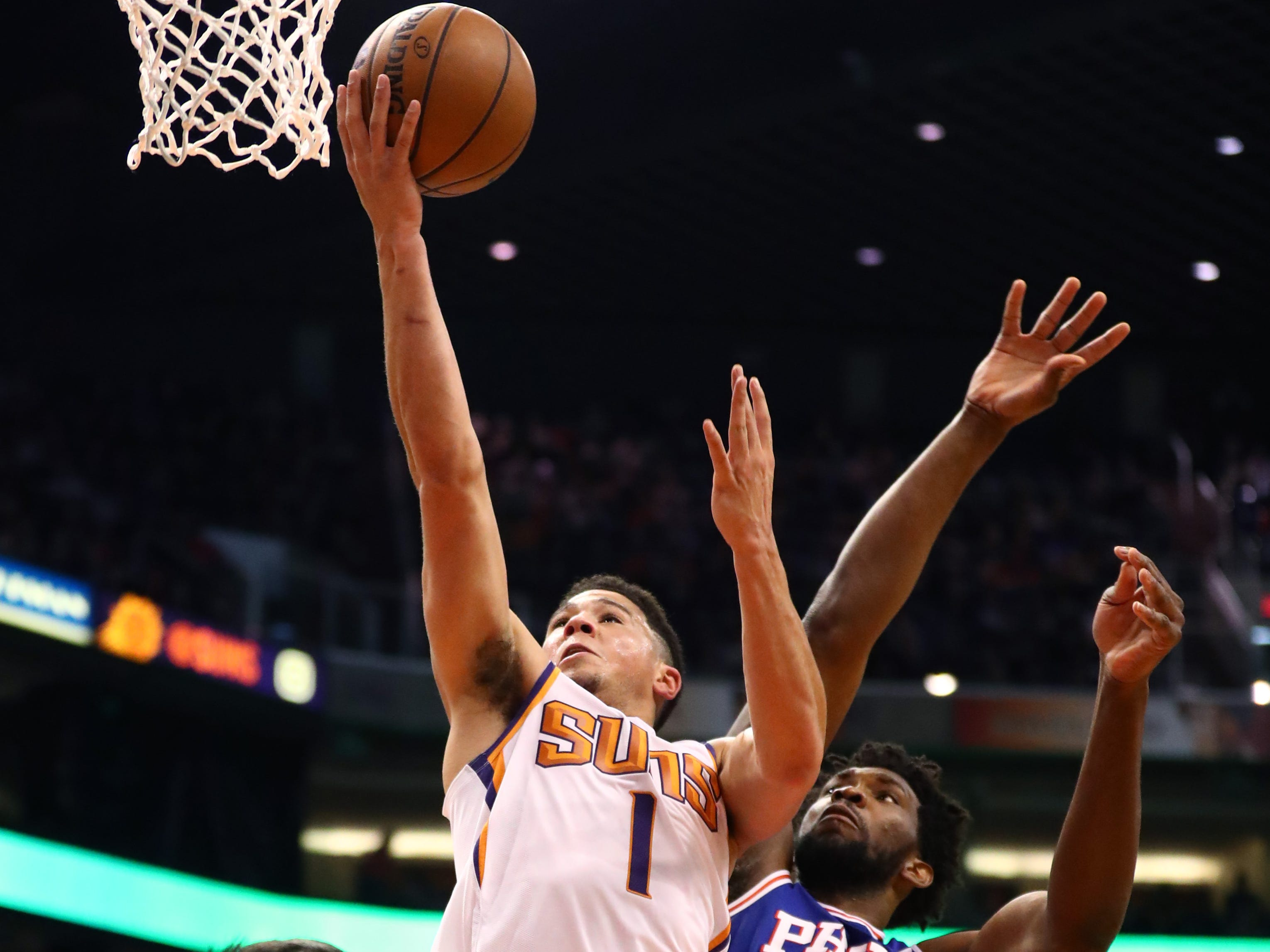 Jan 2, 2019; Phoenix, AZ, USA; Phoenix Suns guard Devin Booker (1) against Philadelphia 76ers center Joel Embiid (21)  in the first half at Talking Stick Resort Arena. Mandatory Credit: Mark J. Rebilas-USA TODAY Sports