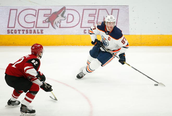 Edmonton Oilers center Connor McDavid (97) looks to pass while defended by Arizona Coyotes defenseman Jordan Oesterle (82) during the third period in Glendale January 2, 2019.