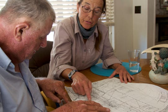 Mike Hayhurst and Holly Richter look at a map in Hayhurst's kitchen after horseback riding along the Babocomari River on June 23, 2018.