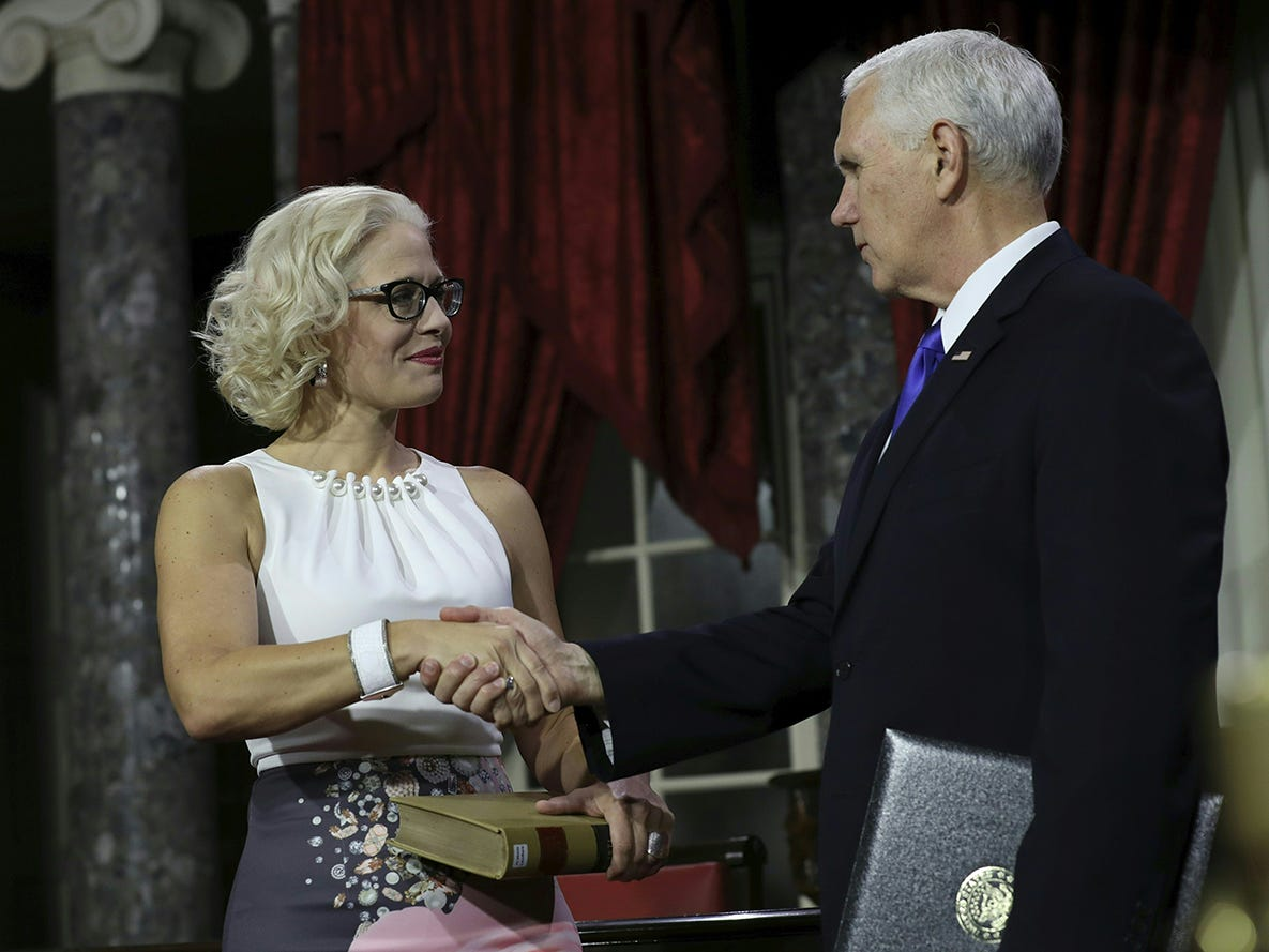 U.S. Sen. Kyrsten Sinema shakes hands with Vice President Mike Pence during the swearing-in re-enactments for recently elected senators in the Old Senate Chamber on Capitol Hill in Washington, D.C., Jan. 3, 2019.