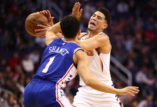 Suns guard Devin Booker is fouled by 76ers guard Landry Shamet during the first half of a game Jan. 2 at Talking Stick Resort Arena.
