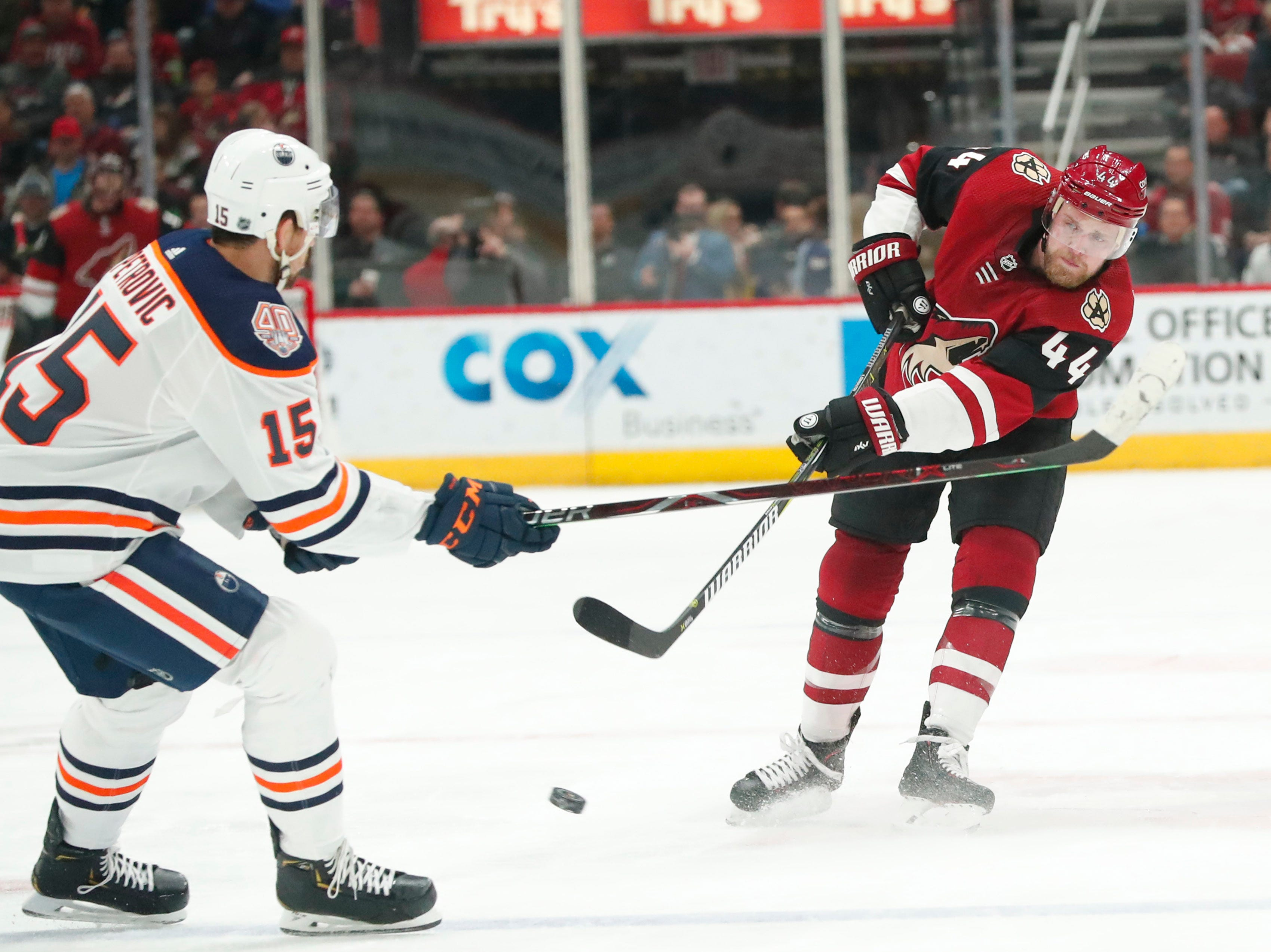 Arizona Coyotes defenseman Kevin Connauton (44) dumps the puck in against Edmonton Oilers defenseman Alexander Petrovic (15) during the second period in Glendale January 2, 2019.