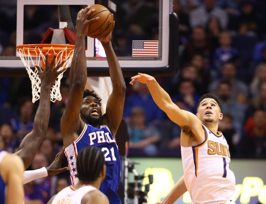 Jan 2, 2019: Philadelphia 76ers center Joel Embiid (21) grabs a pass against Phoenix Suns guard Devin Booker (1) in the second half at Talking Stick Resort Arena.