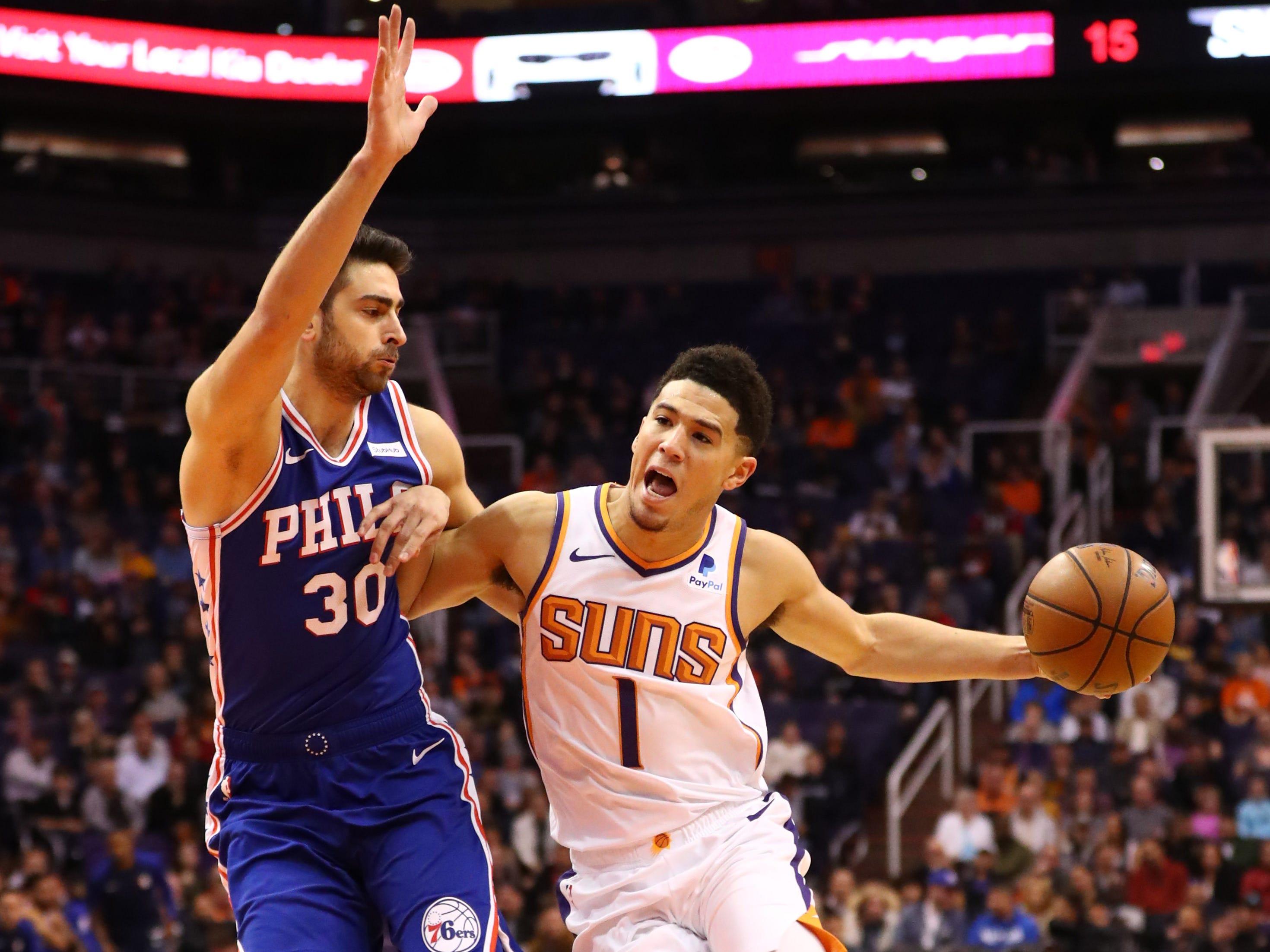 Jan 2, 2019; Phoenix, AZ, USA; Phoenix Suns guard Devin Booker (1) against Philadelphia 76ers guard Furkan Korkmaz (30) in the first half at Talking Stick Resort Arena. Mandatory Credit: Mark J. Rebilas-USA TODAY Sports